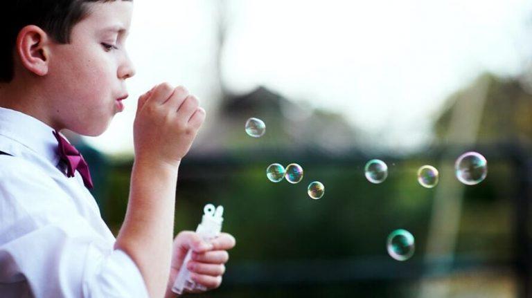 un petit garçon jouant avec des bulles de savon