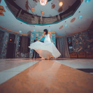 les deux mariés qui dansent dans une grande salle vide
