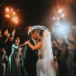des mariés s'embrassent entourés de leurs invités