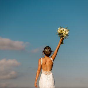 une mariée de dos tient son bouquet de mariage en l'air