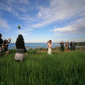 une jeune mariée fait le rituel du lancé de bouquet près de la mer