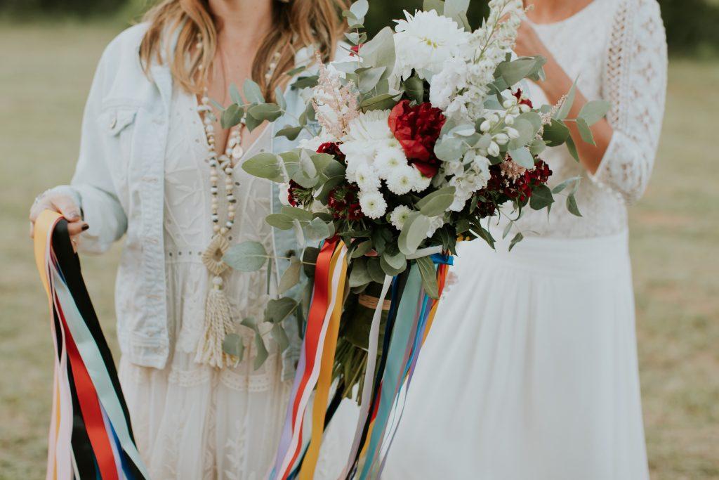 deux mariées tiennent un bouquet et des rubans pour un rituel