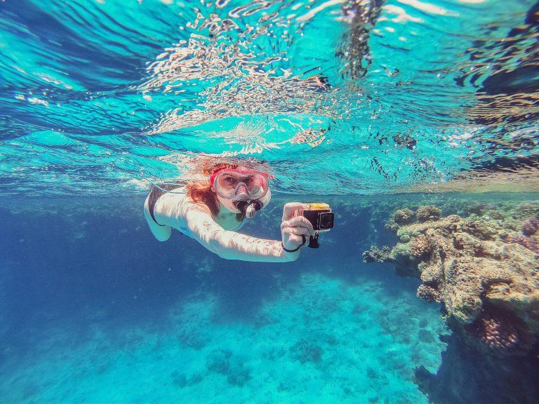 une jeune fille fait du snorkelling avec une caméra