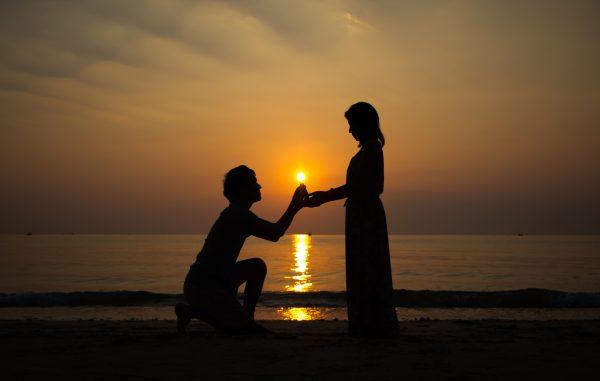 homme qui demande en mariage pendant un coucher de soleil à la mer